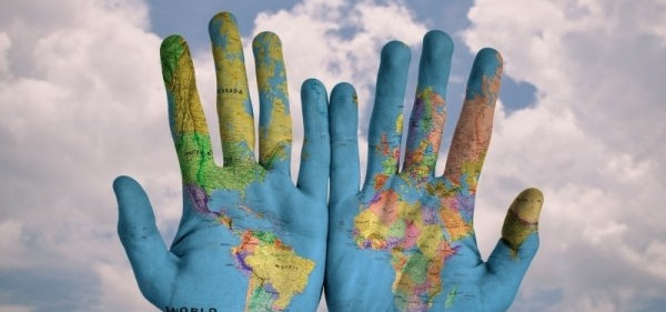 abstract-image-of-human-hands-covered-with-world-map-against-clouds-in-summer-sky